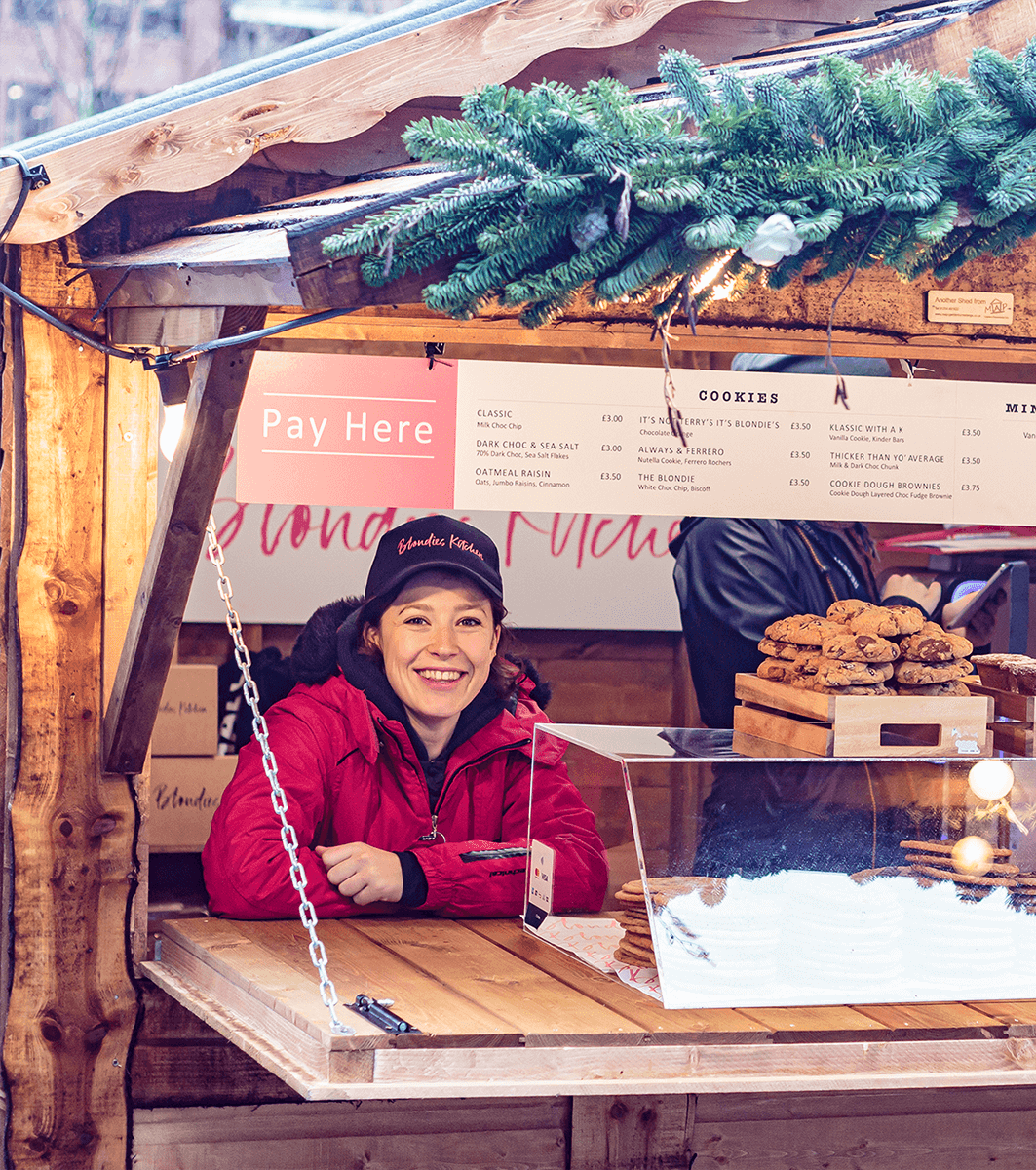 Brunette female brand ambassador wearing a baseball cap working at a Blondies Kitchen pop-up kiosk at London market. There is a selection of cookies on the counter beside her.