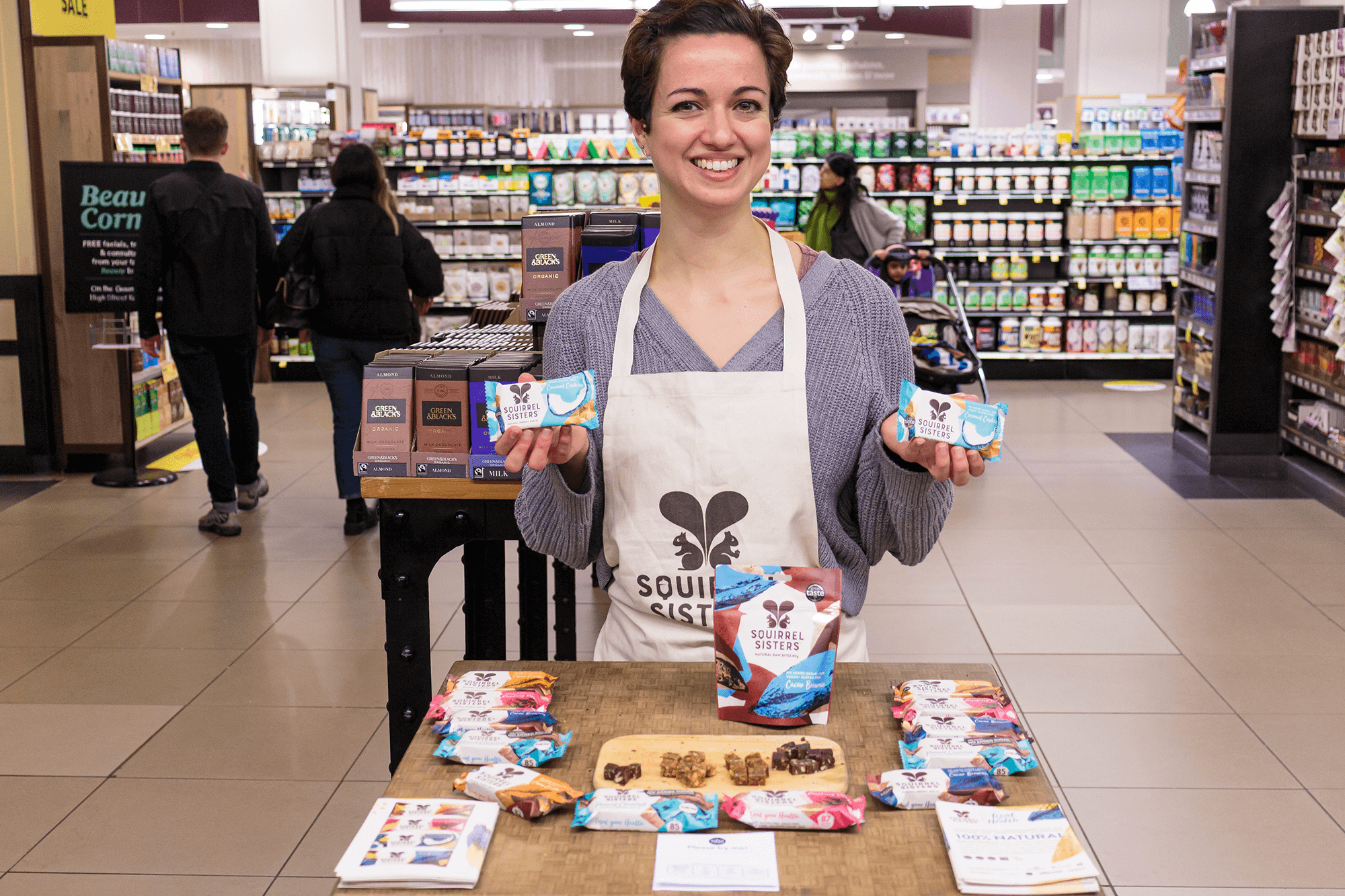 Female brand ambassador with short, dark hair standing behind a table giving out free samples of Squirrel Sisters healthy snack bars.