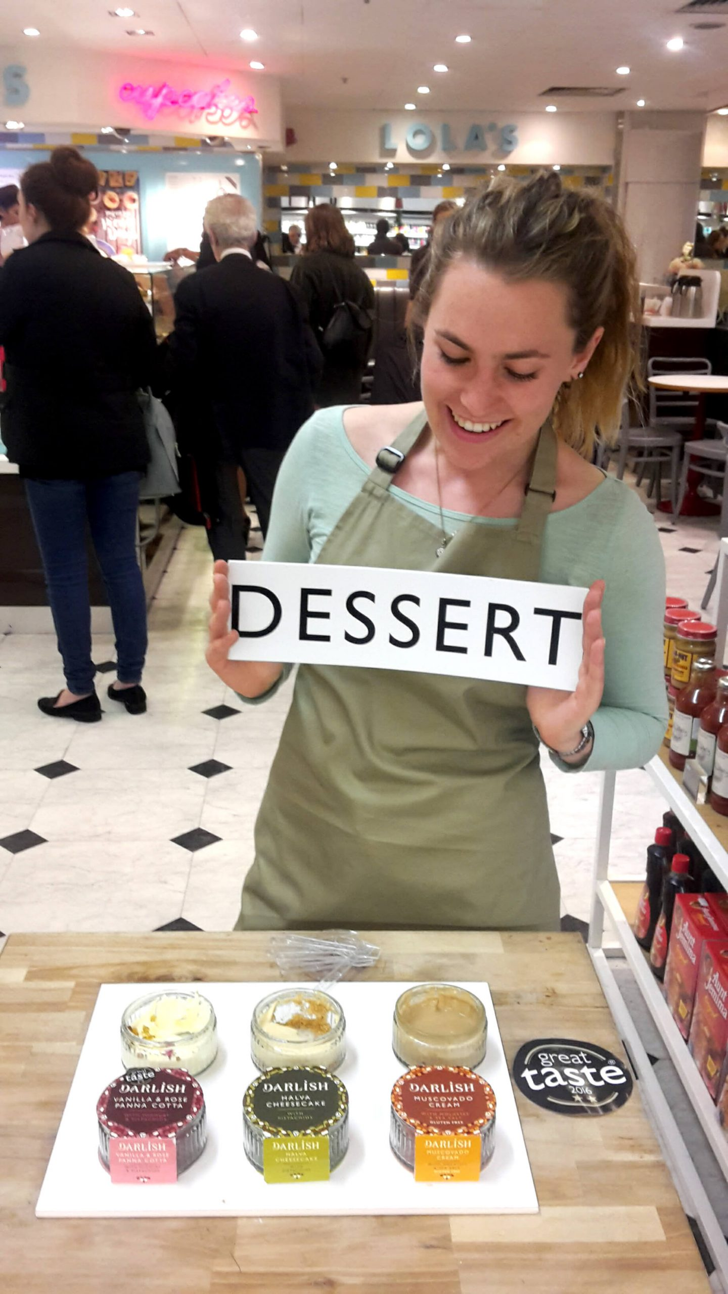 Young blonde woman looking downwards at a black and white 'dessert' sign that she is holding. She is standing behind a table with dessert pots laid out on it.