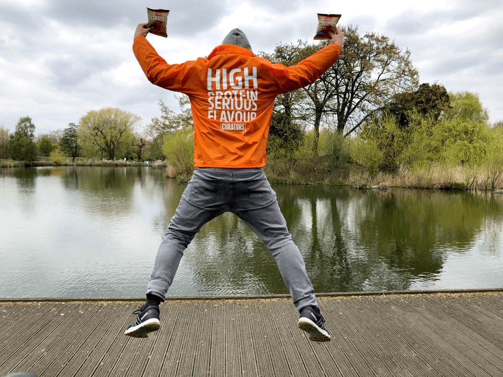 Male with his back facing the camera jumping in the air in a star-jump position. He is wearing an orange waterproof jacket with the words 'High Protein, Serious Flavour, The Curators' on it and holding 2 packets of 'The Curators' Pork puff snacks.