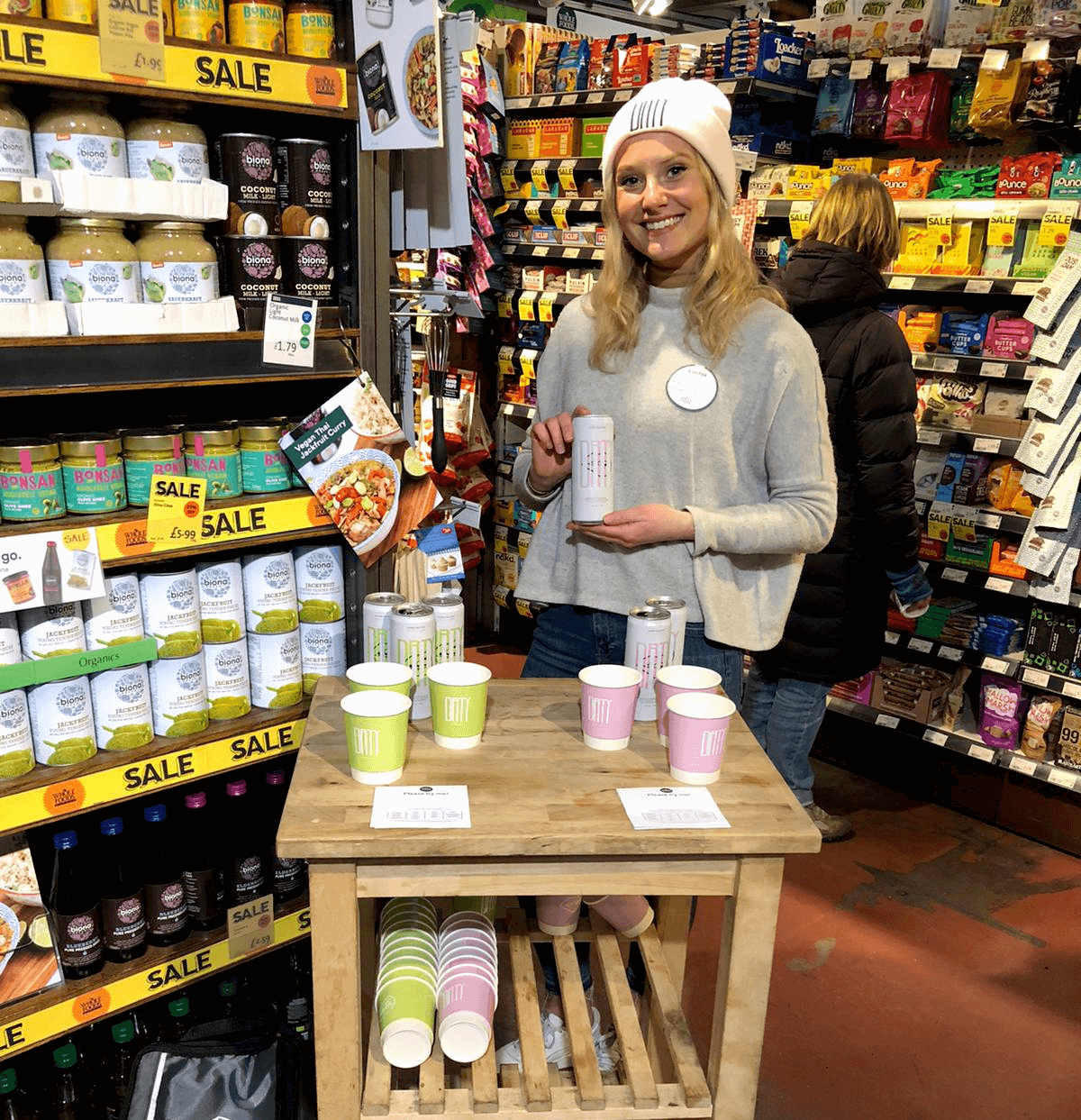 Female brand ambassador with long, blonde hair and wearing a white beanie hat with 'Drty' written on it. She is standing behind a table giving out free samples of Drty Drinks hard seltzer alcohol from cans.
