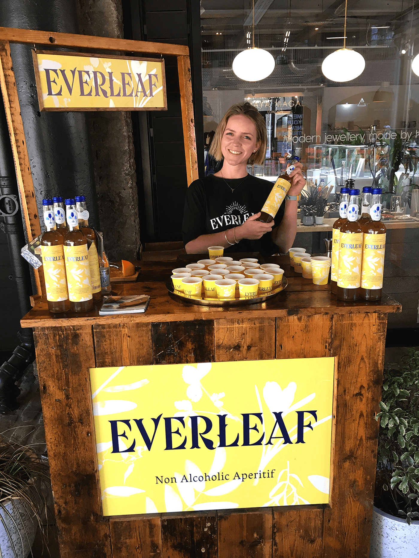 Female brand ambassador with a blonde bob is standing behind a table at an event pouring drinks of Everleaf alcohol-free spirit.