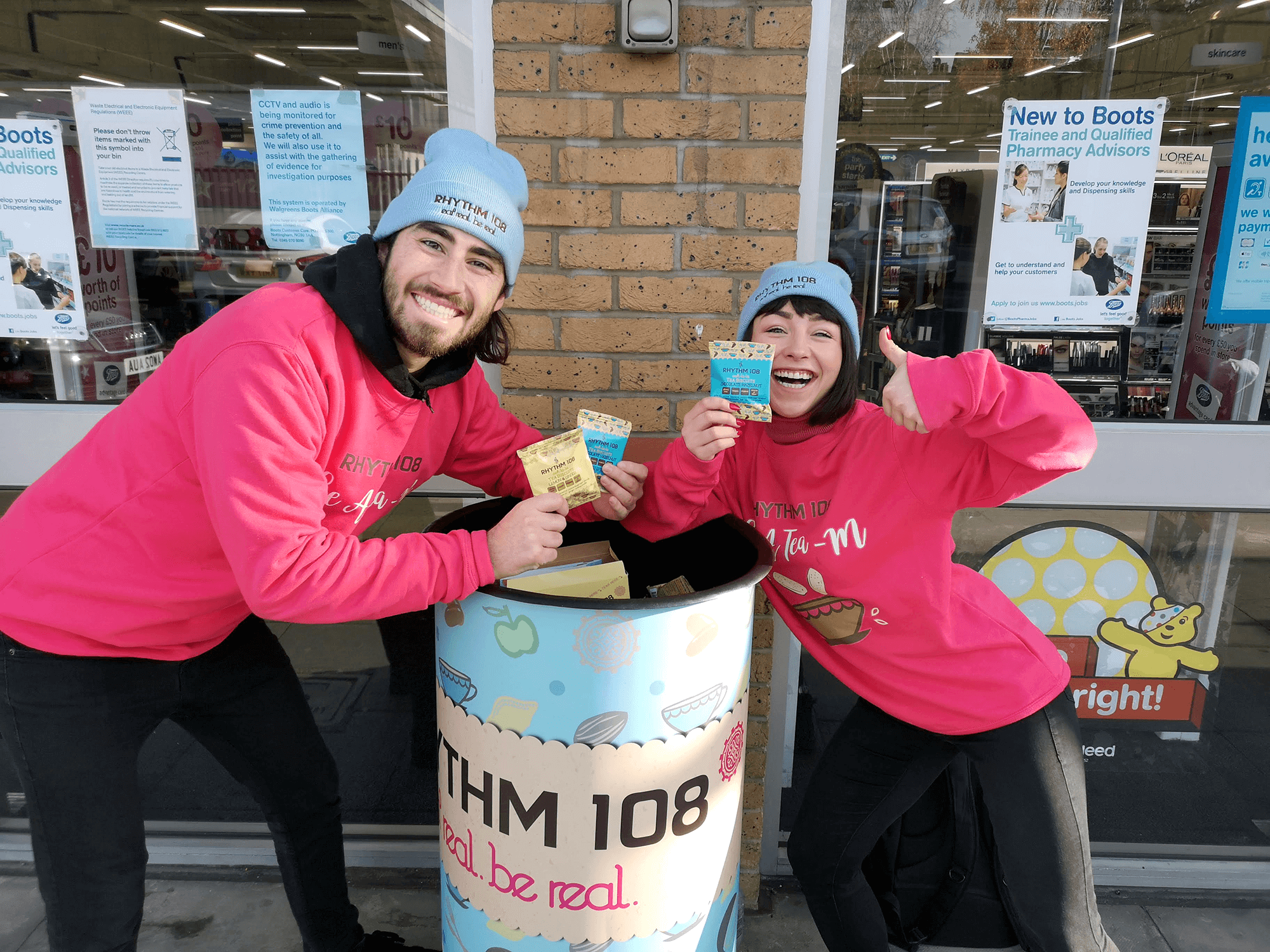 Male and Female brand ambassadors standing outside of Boots store High Holborn. They have a Rhythm108 branded wheelie bin and are giving out free samples of Rhythm108 gluten-free, vegan biscuits to members of the public.